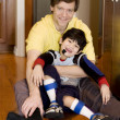 Father holding disabled son on kitchen floor — Stock Photo #9802338