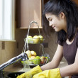 Teen girl washing dishes at kitchen sink — Stock Photo #9802340