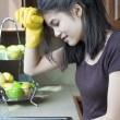 Teen girl washing dishes at kitchen sink, tired expression. — Stock Photo #9802341