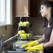 Teen girl washing dishes at kitchen sink — Stok fotoğraf