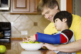 Father helping disabled son with work in the kitchen — Stock Photo