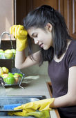 Teen girl washing dishes at kitchen sink, tired expression. — Stock Photo