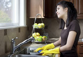 Teen girl washing dishes at kitchen sink — Stock Photo