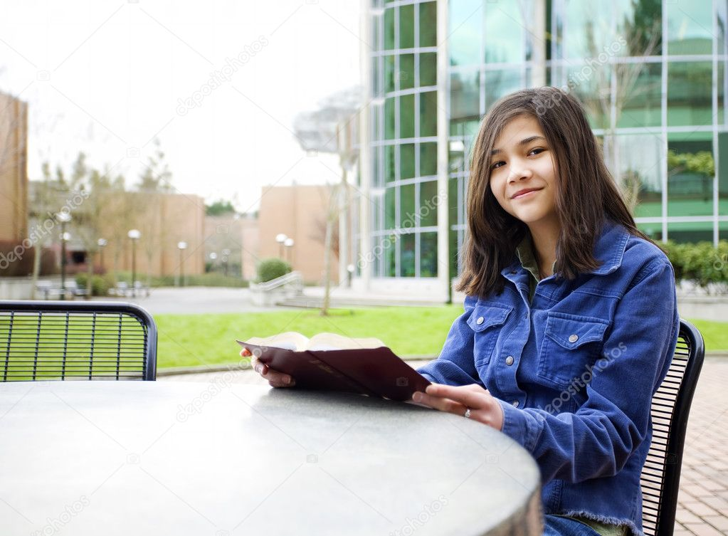Twelve year old biracial girl sitting outdoors reading a book  Stock Photo #9802334