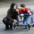 Mother with disabled son in walker - Foto Stock