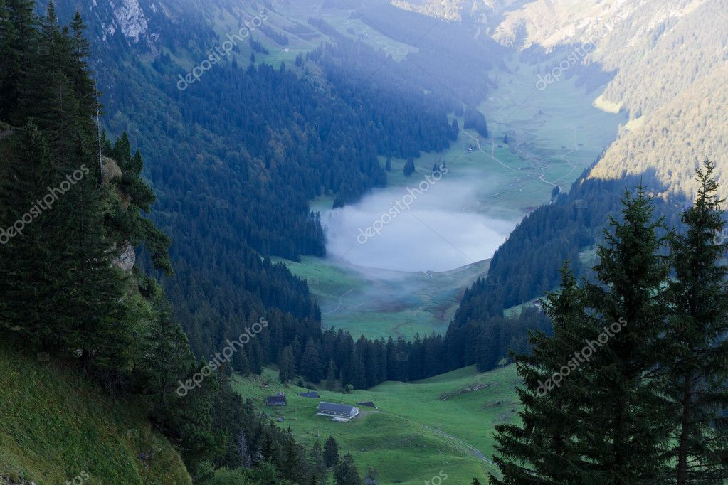 Deep green valley with lake and mist floating on it and mountain peaks reflecting surounded by high,steep, rocky mountain walls at Säntis, Switzerland — Stock Photo #10427348