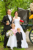 Newlyweds in front of hores carriage — Stock Photo