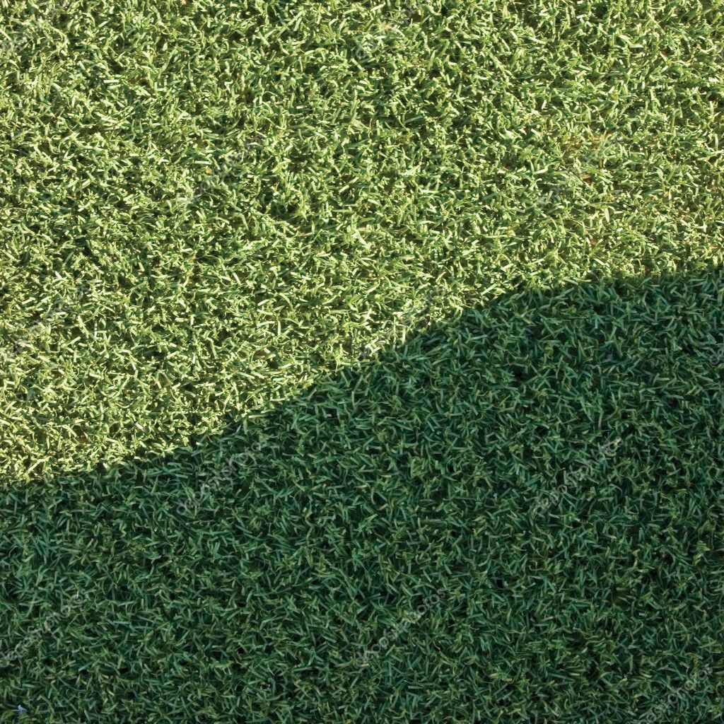 Artificial astroturf grass fake turf synthetic lawn field macro closeup with gentle shaded shadow area, green sports texture background with a shade — Stock Photo #10622269