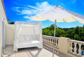 Bed and parasol on the terrace under the sun — Stock Photo