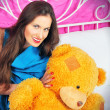 Beautiful young woman on a bed with teddy bear — Stock Photo