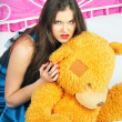 Stock Photo: Beautiful woman sitting on a bed with teddy bear