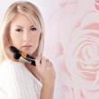 Woman holds the make-up brushes against pink rose background — Stock Photo