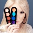Foto Stock: Beautiful young womholding eye shadow palette