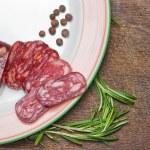Salami on wooden background — Stock Photo