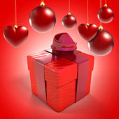 Christmas baubles and hearts with gift box over red background — Stock Photo