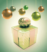 Christmas baubles and hearts with gift box over green background — Stock Photo