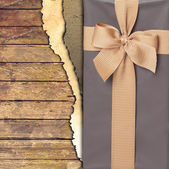 Gift box with ribbon on wooden background — Stock Photo