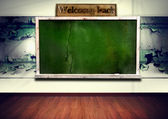 Green blackboard with wooden frame on grunge wall — Stock Photo