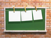 Hanging blank paper on clothesline and green blackboard — Stock Photo