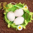 Eggs in green basket on wicker background - Stock Photo