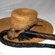 Straw hat with a whip and a wooden smoking pipe - Stock Photo