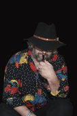 Man in a flowered shirt and a hat with a pipe — Stock Photo