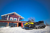 Snowmobile, near a beautiful home — Stock Photo