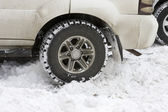 Car tires on a snowy road — Stock Photo