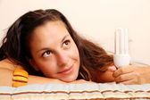 Girl with a energy saver light bulb — Stock Photo