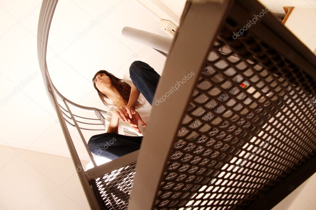 A pensive woman sitting on the stairs. — Stock Photo #9307606