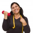 Hispanic Woman with Tape Measure Lifting Dumbbell — Stock Photo #10326736