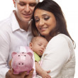 Young Mixed Race Parents with Baby Holding Piggy Bank — Stock Photo