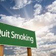 Quit Smoking Green Road Sign and Clouds - Stock Photo