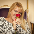 Seated Woman Smiling While Smelling Red Rose - Foto Stock