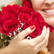 Smiling Woman Holding Bunch of Red Roses — Stock Photo
