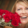 Smiling Blonde Woman with Red Roses - Stock fotografie