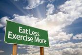 Comer menos sinal de estrada de exercício mais verdes e nuvens — Foto Stock