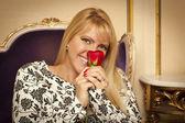 Zittende vrouw die lacht terwijl ruiken rode roos — Stockfoto