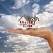 Model House in Female Hand on Sky Background — Stock Photo