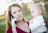 Attractive Woman Using Cell Phone with Child — Stock Photo