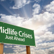 Midlife Crises Just Ahead Green Road Sign and Clouds - Stock Photo
