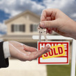 Handing Over the House Keys in Front of Sold New Home — Stock Photo #9433404