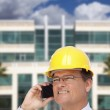 Contractor in Hardhat Talks on Phone In Front of Building — Stock Photo #9539299