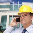 Contractor in Hardhat Talks on Phone In Front of Building - Stock Photo