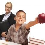rapaz estudante latino-americanos com maçã e fêmea adulta behind — Foto Stock