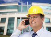 Contractor in Hardhat Talks on Phone In Front of Building — Stock Photo