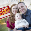 Happy Young Family in Front of Sold Real Estate Sign — Stock Photo #9571501