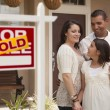Stock Photo: Hispanic Family in Front of Home with Sold Real Estate Sign