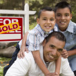 Hispanic Father and Sons in Front of Sold Real Estate Sign — Stockfoto