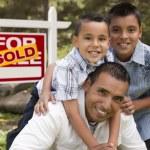 hispânico pai e filhos na frente de sinal de imóveis vendidos — Foto Stock